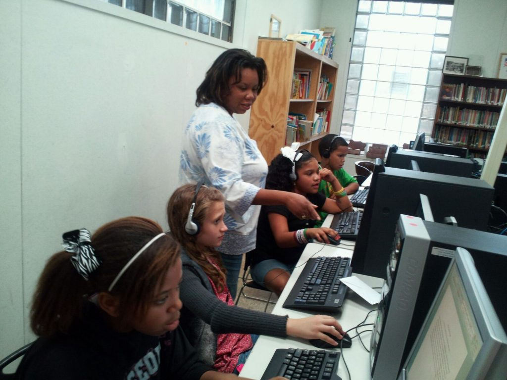 Cultural Teacher helping four students on computers