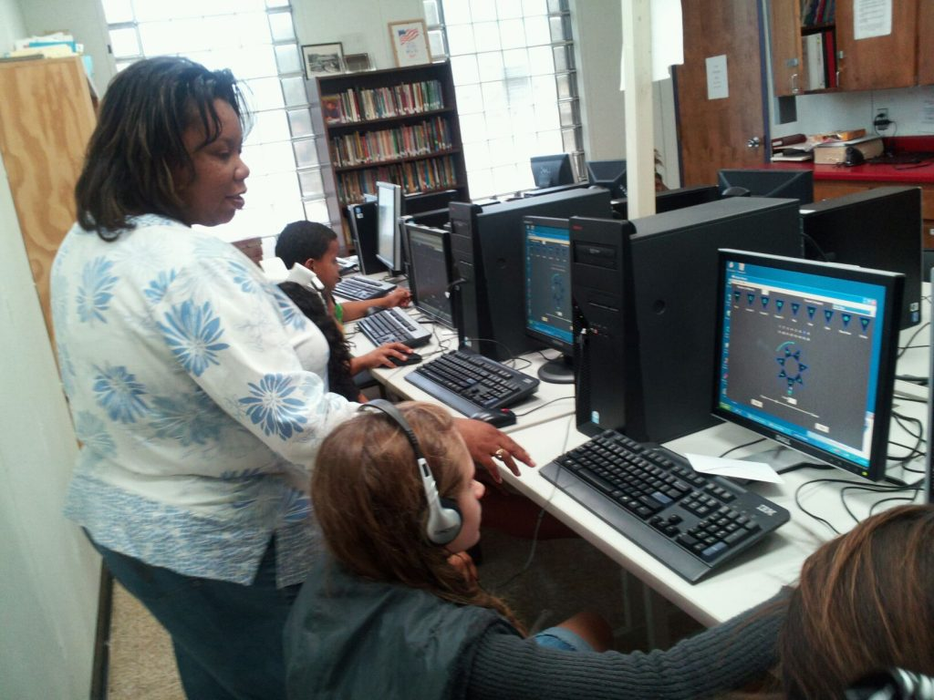 Teacher helping one of four students in a computer lab
