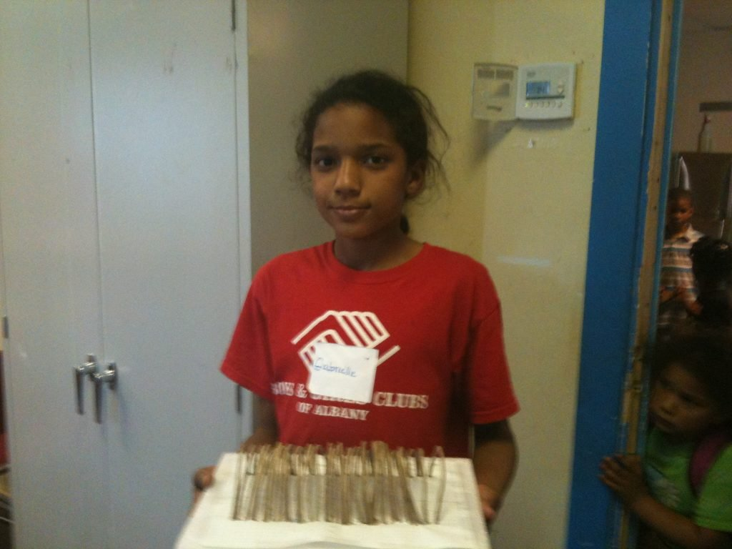 Young girl in a red shirt showing her styrofoam project