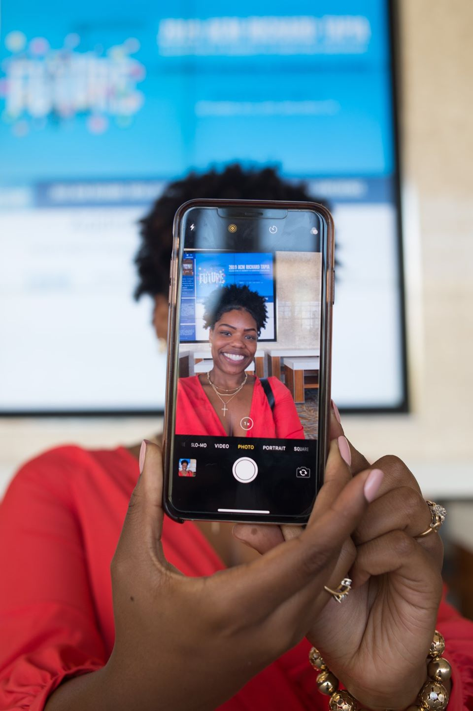 Lady taking a photo of herself with the front of the phone facing towards the camera